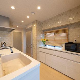 他の地域の中サイズのコンテンポラリースタイルのおしゃれなII型キッチン (一体型シンク、フラットパネル扉のキャビネット、白いキャビネット、グレーのキッチンパネル、ガラスタイルのキッチンパネル、ベージュの床、白いキッチンカウンター) の写真