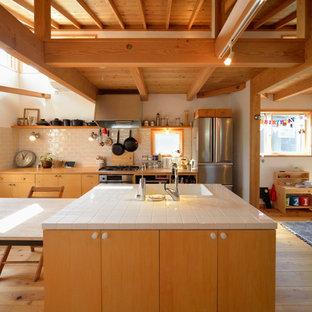 他の地域のコンテンポラリースタイルのおしゃれなキッチン (ドロップインシンク、フラットパネル扉のキャビネット、中間色木目調キャビネット、タイルカウンター、ベージュキッチンパネル、サブウェイタイルのキッチンパネル、シルバーの調理設備、無垢フローリング、茶色い床) の写真