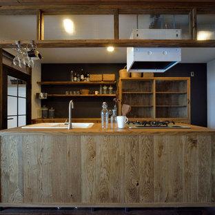 他の地域のアジアンスタイルのおしゃれなアイランドキッチン (ドロップインシンク、フラットパネル扉のキャビネット、中間色木目調キャビネット、木材カウンター、濃色無垢フローリング、茶色い床) の写真