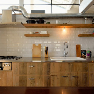 他の地域のコンテンポラリースタイルのおしゃれなキッチン (シングルシンク、フラットパネル扉のキャビネット、中間色木目調キャビネット、ステンレスカウンター、白いキッチンパネル、セラミックタイルのキッチンパネル、無垢フローリング、茶色い床) の写真
