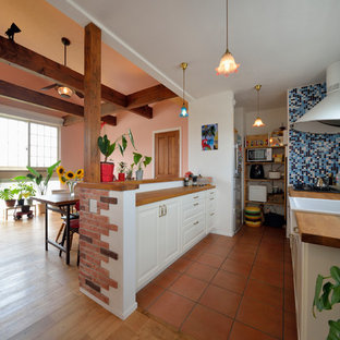 Design ideas for an asian single-wall open plan kitchen in Other with a farmhouse sink, raised-panel cabinets, white cabinets, wood benchtops, terra-cotta floors, a peninsula and brown floor.