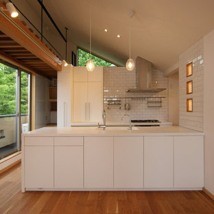 他の地域の北欧スタイルのおしゃれなキッチン (一体型シンク、フラットパネル扉のキャビネット、白いキャビネット、無垢フローリング、茶色い床、白いキッチンパネル、白い調理設備、白いキッチンカウンター) の写真