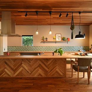 他の地域のアジアンスタイルのおしゃれなキッチン (フラットパネル扉のキャビネット、中間色木目調キャビネット、木材カウンター、緑のキッチンパネル、サブウェイタイルのキッチンパネル、無垢フローリング、茶色い床、ベージュのキッチンカウンター) の写真