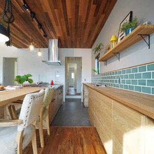 他の地域のアジアンスタイルのおしゃれなキッチン (フラットパネル扉のキャビネット、ベージュのキャビネット、木材カウンター、緑のキッチンパネル、ガラスタイルのキッチンパネル、パネルと同色の調理設備、濃色無垢フローリング、茶色い床、ベージュのキッチンカウンター) の写真