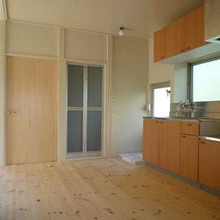 他の地域の小さいアジアンスタイルのおしゃれなキッチン (シングルシンク、インセット扉のキャビネット、茶色いキャビネット、ステンレスカウンター、メタリックのキッチンパネル、白い調理設備、淡色無垢フローリング、アイランドなし、ベージュの床) の写真