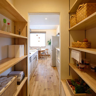 Inspiration for a mid-sized scandinavian single-wall kitchen pantry in Other with an integrated sink, white cabinets, solid surface benchtops, white splashback, glass sheet splashback, medium hardwood floors, white benchtop and brown floor.