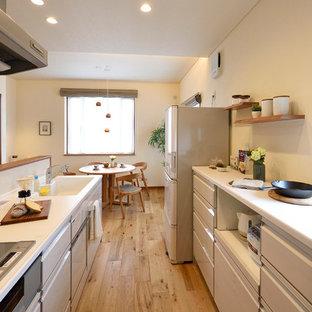 他の地域の中サイズのモダンスタイルのおしゃれなキッチン (一体型シンク、白いキャビネット、人工大理石カウンター、白いキッチンパネル、ガラス板のキッチンパネル、無垢フローリング、白いキッチンカウンター、フラットパネル扉のキャビネット、茶色い床) の写真