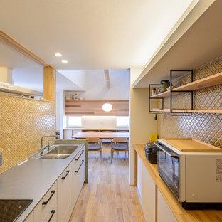 他の地域のエクレクティックスタイルのおしゃれなキッチン (シングルシンク、フラットパネル扉のキャビネット、白いキャビネット、ステンレスカウンター、茶色いキッチンパネル、淡色無垢フローリング、茶色い床) の写真