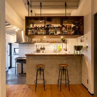 他の地域のインダストリアルスタイルのおしゃれなキッチン (木材カウンター、白いキッチンパネル、シルバーの調理設備、グレーの床、茶色いキッチンカウンター、オープンシェルフ、濃色木目調キャビネット) の写真