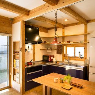 Cette image montre une cuisine ouverte asiatique en L avec un évier intégré, un placard à porte plane, des portes de placard noires, un sol en bois brun, une péninsule et un sol marron.