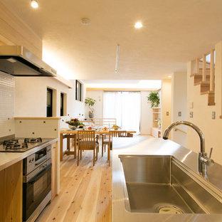 横浜のアジアンスタイルのおしゃれなアイランドキッチン (シングルシンク、フラットパネル扉のキャビネット、中間色木目調キャビネット、ステンレスカウンター、白いキッチンパネル、淡色無垢フローリング、茶色い床) の写真