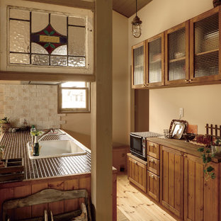 他の地域のカントリー風おしゃれなキッチン (ドロップインシンク、落し込みパネル扉のキャビネット、中間色木目調キャビネット、タイルカウンター、淡色無垢フローリング、茶色い床) の写真
