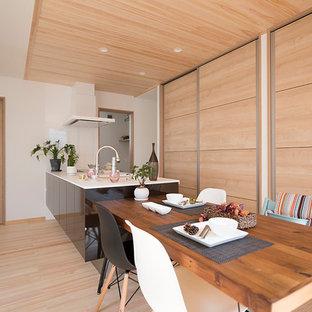 他の地域のコンテンポラリースタイルのおしゃれなキッチン (一体型シンク、フラットパネル扉のキャビネット、黒いキャビネット、淡色無垢フローリング、ベージュの床) の写真