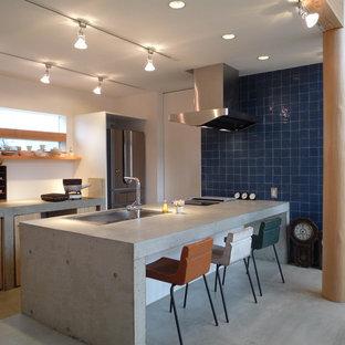 他の地域のアジアンスタイルのおしゃれなキッチン (ドロップインシンク、フラットパネル扉のキャビネット、淡色木目調キャビネット、コンクリートカウンター、シルバーの調理設備、コンクリートの床、グレーの床、グレーのキッチンカウンター) の写真