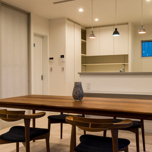 This is an example of a medium sized modern l-shaped kitchen/diner in Other with a single-bowl sink, beaded cabinets, white cabinets, engineered stone countertops, white splashback, glass sheet splashback, stainless steel appliances, plywood flooring and white floors.