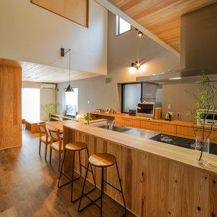 他の地域の和風のおしゃれなペニンシュラキッチン (シングルシンク、フラットパネル扉のキャビネット、中間色木目調キャビネット、ステンレスカウンター、濃色無垢フローリング、茶色い床、茶色いキッチンカウンター) の写真