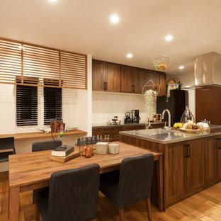 Idéer för att renovera ett orientaliskt kök, med en integrerad diskho, skåp i shakerstil, skåp i mörkt trä, bänkskiva i rostfritt stål, vitt stänkskydd, svarta vitvaror, ljust trägolv, en köksö och beiget golv