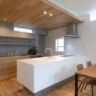 Inspiration for a modern single-wall open plan kitchen in Other with an integrated sink, flat-panel cabinets, medium wood cabinets, medium hardwood floors, a peninsula and brown floor.