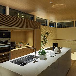 Inredning av ett modernt beige linjärt beige kök med öppen planlösning, med en undermonterad diskho, vita skåp, bänkskiva i kvarts, rostfria vitvaror, travertin golv, en köksö och beiget golv