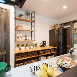 他の地域の北欧スタイルのおしゃれなキッチン (一体型シンク、ステンレスカウンター、茶色いキッチンカウンター) の写真