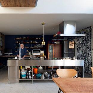 札幌のインダストリアルスタイルのおしゃれなアイランドキッチン (シングルシンク、オープンシェルフ、ステンレスカウンター、コンクリートの床、緑の床) の写真