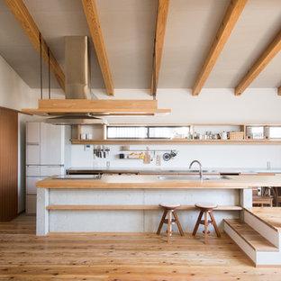 他の地域の中サイズのモダンスタイルのおしゃれなキッチン (アンダーカウンターシンク、フラットパネル扉のキャビネット、中間色木目調キャビネット、木材カウンター、白いキッチンパネル、シルバーの調理設備の、無垢フローリング、茶色い床、茶色いキッチンカウンター) の写真