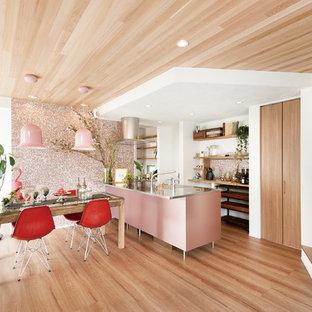 他の地域のインダストリアルスタイルのおしゃれなキッチン (ステンレスカウンター、ピンクのキッチンパネル、一体型シンク、黒い調理設備、茶色い床、無垢フローリング) の写真