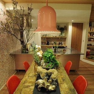 Imagen de cocina lineal, industrial, abierta, con fregadero integrado, encimera de acero inoxidable, salpicadero rosa, electrodomésticos negros, península y suelo marrón