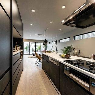 Пример оригинального дизайна: отдельная, линейная кухня среднего размера в современном стиле с монолитной раковиной, черными фасадами, столешницей из переработанного стекла, коричневым фартуком, техникой под мебельный фасад, полом из фанеры, островом, серым полом, белой столешницей и плоскими фасадами
