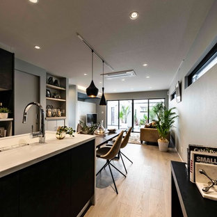Medium sized modern single-wall enclosed kitchen in Other with an integrated sink, glass-front cabinets, black cabinets, composite countertops, brown splashback, integrated appliances, plywood flooring, an island, grey floors and white worktops.