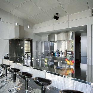 他の地域のコンテンポラリースタイルのおしゃれなキッチン (一体型シンク、フラットパネル扉のキャビネット、ステンレスカウンター、グレーの床) の写真