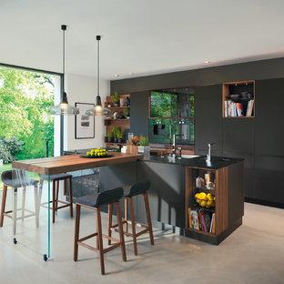 Modelo de cocina comedor lineal, actual, de tamaño medio, con armarios con paneles lisos, puertas de armario negras, una isla y suelo verde