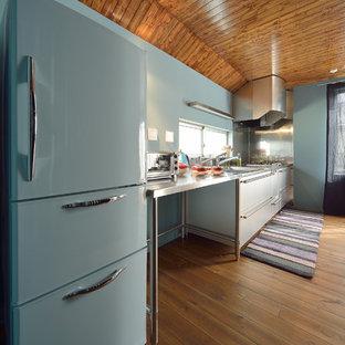 他の地域のエクレクティックスタイルのおしゃれなI型キッチン (フラットパネル扉のキャビネット、白いキャビネット、ステンレスカウンター、青いキッチンパネル、無垢フローリング、茶色い床) の写真