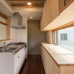 東京23区のアジアンスタイルのおしゃれなII型キッチン (一体型シンク、フラットパネル扉のキャビネット、淡色木目調キャビネット、ステンレスカウンター、ガラスまたは窓のキッチンパネル、パネルと同色の調理設備、濃色無垢フローリング、茶色い床、グレーのキッチンカウンター) の写真
