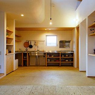 アジアンスタイルのおしゃれなキッチン (一体型シンク、オープンシェルフ、ステンレスカウンター、白いキッチンパネル、茶色い床) の写真