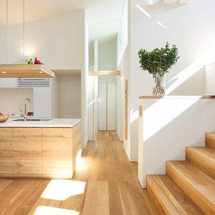他の地域の北欧スタイルのおしゃれなキッチン (アンダーカウンターシンク、フラットパネル扉のキャビネット、淡色木目調キャビネット、人工大理石カウンター、白いキッチンパネル、シルバーの調理設備の、淡色無垢フローリング) の写真