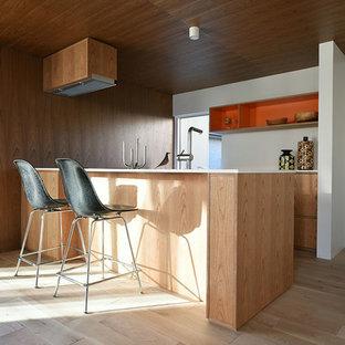 他の地域の中サイズのミッドセンチュリースタイルのおしゃれなキッチン (アンダーカウンターシンク、フラットパネル扉のキャビネット、中間色木目調キャビネット、人工大理石カウンター、木材のキッチンパネル、シルバーの調理設備の、淡色無垢フローリング、白いキッチンカウンター、ベージュの床) の写真