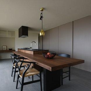 他の地域の中サイズのモダンスタイルのおしゃれなキッチン (アンダーカウンターシンク、フラットパネル扉のキャビネット、濃色木目調キャビネット、御影石カウンター、黒い調理設備、無垢フローリング、グレーの床、黒いキッチンカウンター) の写真