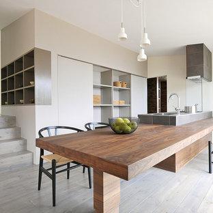 Ejemplo de cocina lineal, minimalista, grande, abierta, con fregadero bajoencimera, puertas de armario de madera en tonos medios, encimera de azulejos, salpicadero blanco, electrodomésticos de acero inoxidable, suelo de madera clara, una isla, suelo gris y encimeras marrones