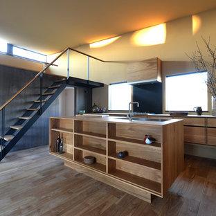 他の地域の大きいおしゃれなキッチン (アンダーカウンターシンク、淡色木目調キャビネット、木材カウンター、黒いキッチンパネル、シルバーの調理設備の、淡色無垢フローリング) の写真