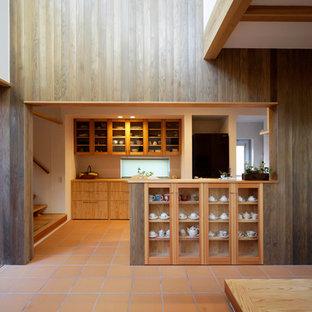 Réalisation d'une cuisine asiatique avec un sol en carreau de terre cuite et un sol orange.