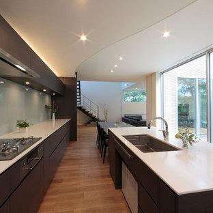 札幌のコンテンポラリースタイルのおしゃれなキッチン (シングルシンク、フラットパネル扉のキャビネット、濃色木目調キャビネット、白いキッチンパネル、無垢フローリング) の写真