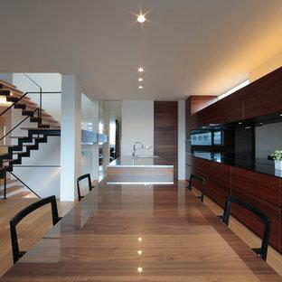 札幌のモダンスタイルのおしゃれなキッチン (一体型シンク、フラットパネル扉のキャビネット、濃色木目調キャビネット、ステンレスカウンター、淡色無垢フローリング、ベージュの床) の写真