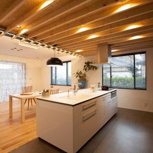 他の地域の広いモダンスタイルのおしゃれなキッチン (白いキャビネット、人工大理石カウンター、セメントタイルの床、黒い床、一体型シンク) の写真
