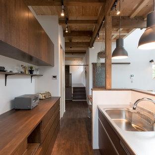札幌の中サイズのアジアンスタイルのおしゃれなキッチン (濃色木目調キャビネット、ステンレスカウンター、濃色無垢フローリング、フラットパネル扉のキャビネット、一体型シンク、白いキッチンパネル、黒い調理設備) の写真
