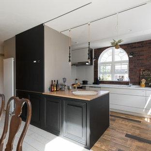 札幌のコンテンポラリースタイルのおしゃれなキッチン (一体型シンク、フラットパネル扉のキャビネット、白いキャビネット、茶色いキッチンパネル、レンガのキッチンパネル、塗装フローリング、茶色い床、黒いキッチンカウンター) の写真