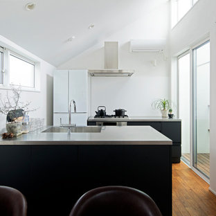 This is an example of a contemporary galley kitchen in Tokyo with an integrated sink, stainless steel benchtops, blue splashback, black appliances, medium hardwood floors, with island, brown floor and blue benchtop.