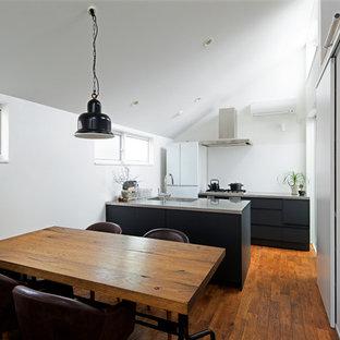 東京23区のコンテンポラリースタイルのおしゃれなキッチン (一体型シンク、フラットパネル扉のキャビネット、黒いキャビネット、白い調理設備、無垢フローリング、ステンレスカウンター、青いキッチンパネル、茶色い床) の写真
