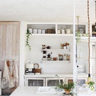 他の地域の小さいシャビーシック調のおしゃれなペニンシュラキッチン (ドロップインシンク、ガラス扉のキャビネット、白いキャビネット、白いキッチンパネル) の写真