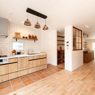 京都のアジアンスタイルのおしゃれなキッチン (シングルシンク、フラットパネル扉のキャビネット、淡色木目調キャビネット、白いキッチンパネル、セラミックタイルのキッチンパネル、テラコッタタイルの床、茶色い床) の写真